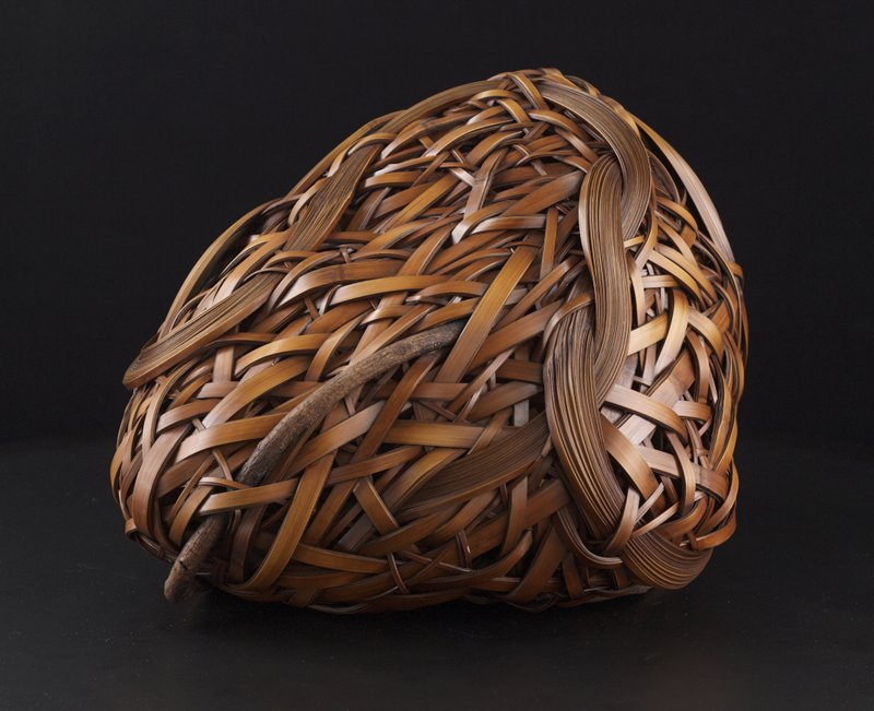 irregularly shaped, mountain-like form; closely woven with overlapping bamboo strips; wide bands of thin, stacked bamboo strips wind through the form; small branches on sides