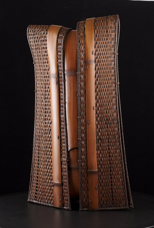 vertical tunic-shaped woven vessel; vertical weave; three vertical bands of bamboo wrap around form, one down center, and one on each side; one side of form is slightly higher than the other