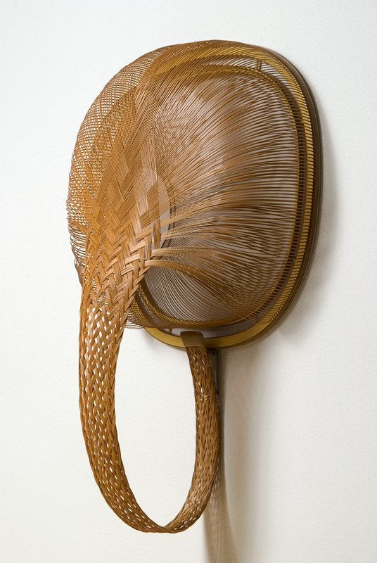 irregularly round, double-walled with braided loop; resembles back of head with braided hair