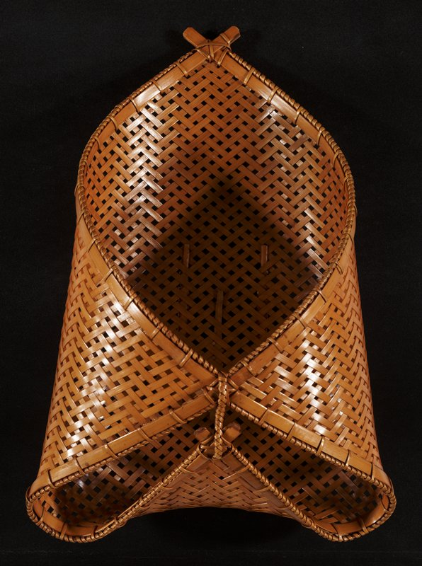 honey colored basket with three corners folded upward and connected forming a somewhat closed parcel; openwork crisscrossing weave; small, dark lacquered bamboo dish
