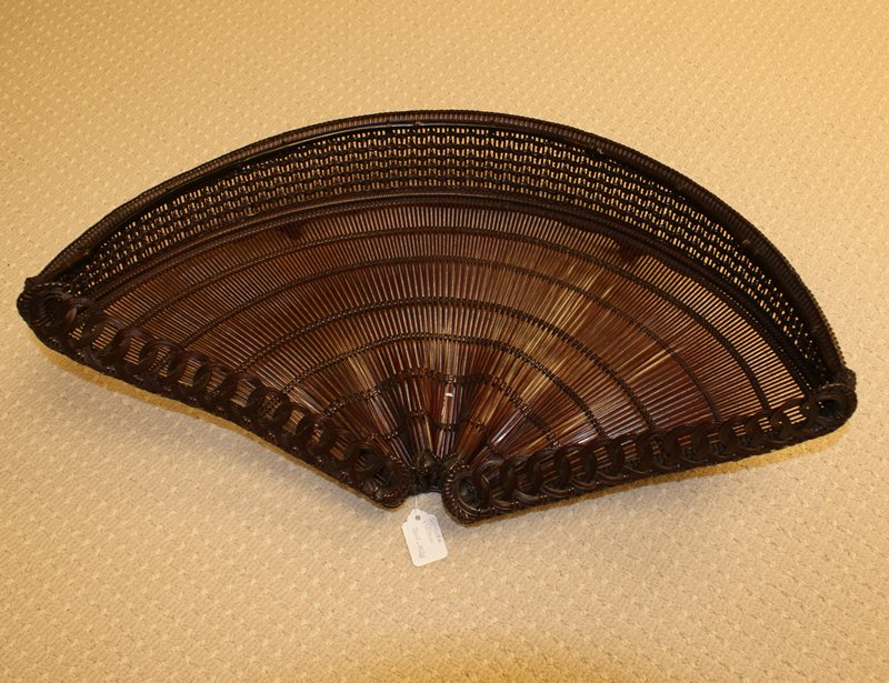 """open fan-shaped basket with open weave; basket slopes downward toward curved edge; gathered ripples at upper center of """"fan""""; raised lip at bottom with closed, decorative weave"""