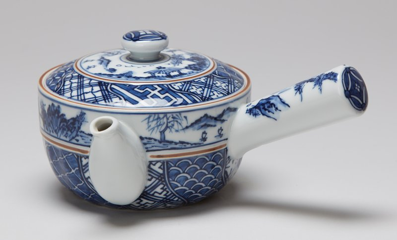 teapot with spout and handle at ninety degree angle; rich blue and white patterns around teapot; decorated band below lip featuring figures playing board game in a garden; pavilion; figure crossing bridges; figure standing on cliff overlooking waterfall on handle; similar scenes on lid