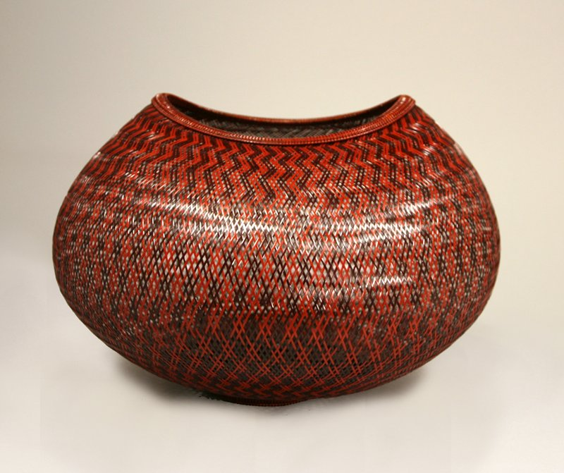 slightly irregular round form with irregular oval mouth; crisscrossing diamond weave of red-brown and orange-brown strips forming zigzag motif
