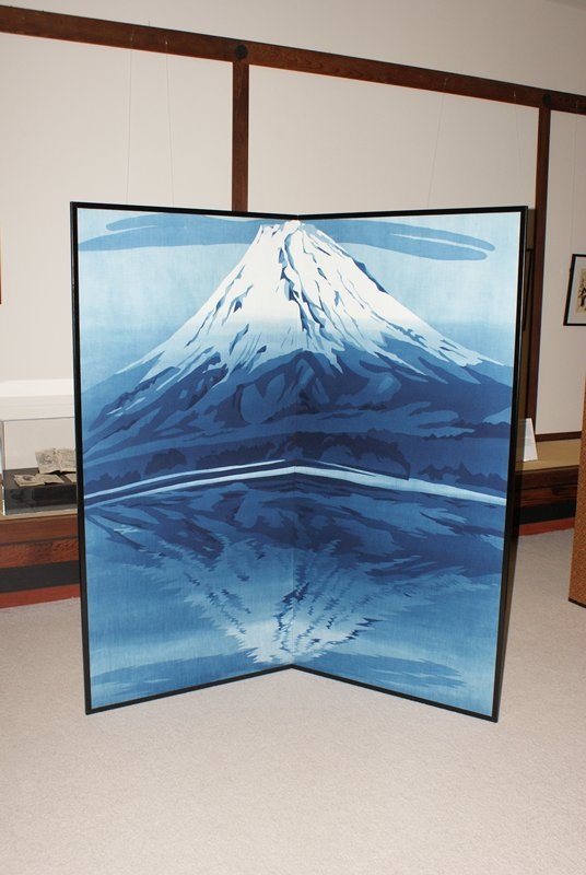 image of Mt. Fuji in blue tones at upper center; image reflected in rippled water below; narrow blue cloud cuts across top
