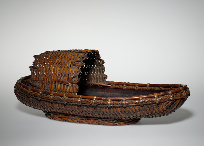 "boat shaped flower basket with arching, woven ""canopy"" at one end with rattan loops; oblong copper tray insert with lacquer-like patina"