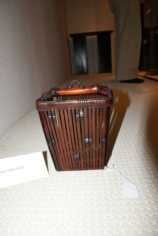 vertically oriented rectangular basket; square base widening to larger square mouth; low handle nearly flush with top made of one thick piece of bamboo with woven hook at center; vertical weave pattern; copper lined bamboo cylinder