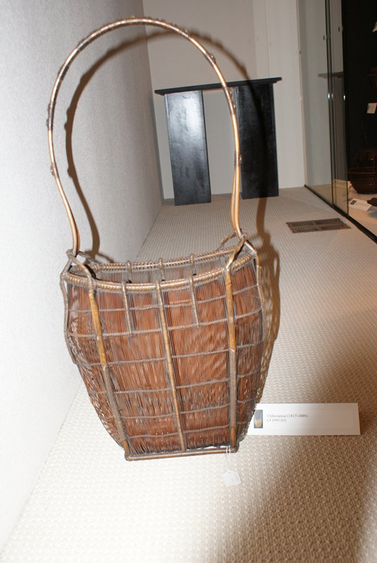 narrow oval basket with rectangular base; bowed sides; open weave with bamboo supports; shorter bamboo supports near top; organic, curving handle; bamboo cylinder mounted to flat base