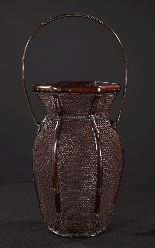 hexagonal basket with bulbous sides; open, star patterned weave; stout handle; large bamboo cylinder