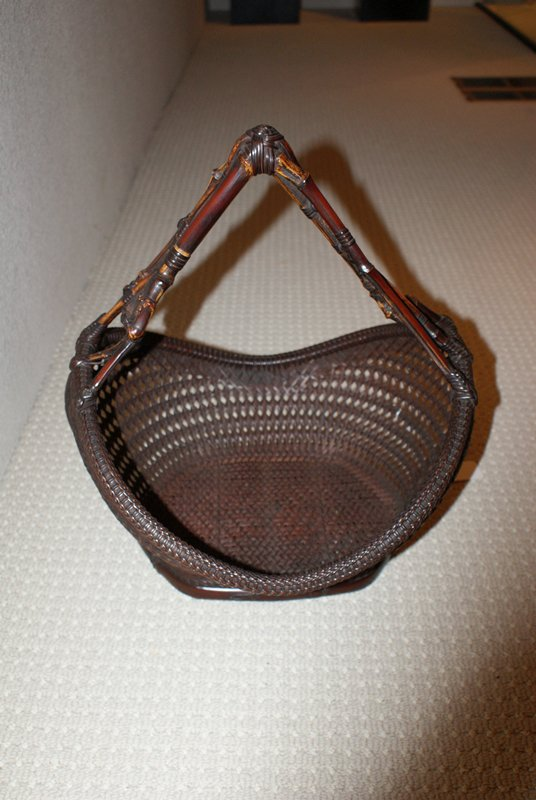short, squat, crescent-shaped flower basket with low dipping front and back; open, crisscross weave with closely woven horizontal elements; handle made of three nearly symmetrical, crooked bamboo branches that come to a steep peak in the middle; oblong, deep copper flower tray in center