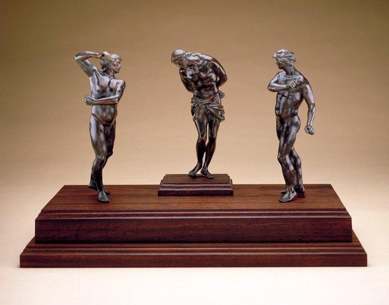 Three nude male figures mounted on one walnut base.