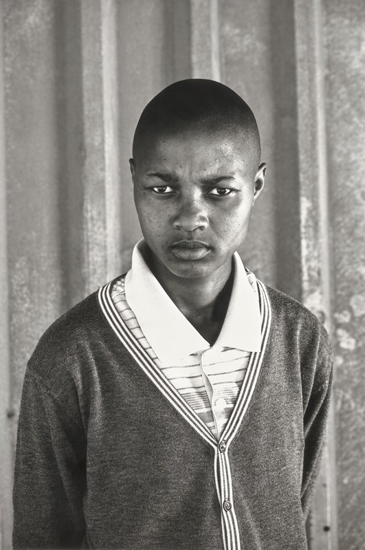 young person viewed from lower torso up; wearning v-neck cardigan sweater and collared polo shirt; serious expression