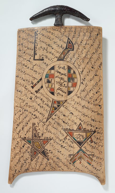 wooden board with leather-covered handle at top; designs in black, yellow, green and orange; one side decorated with bird with circular body, five pointed star and triangle with L-shaped element (abstracted bird motif), with text overall at diagonals in background; same types on motifs on opposite side birds with round bodies and turtle with round body and diamond with text in background with similar design to first side