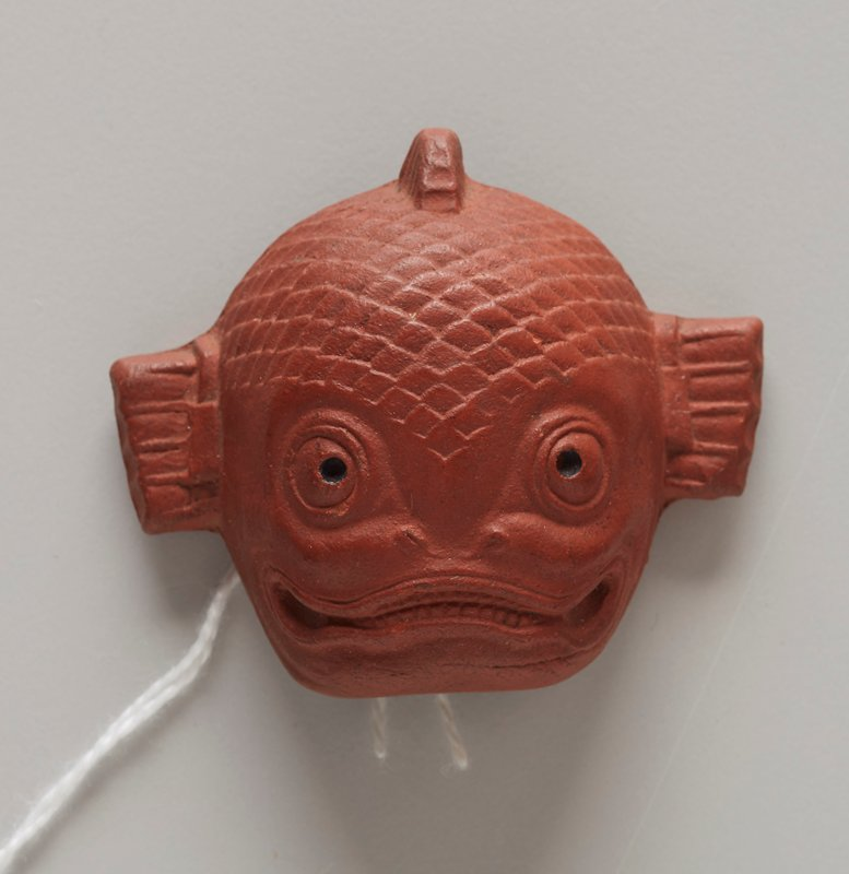 netsuke in the form of a mask; red clay; fish face with fins on either side of head and top of head; flat nostrils; wide smiling mouth with many small teeth; wide round eyes