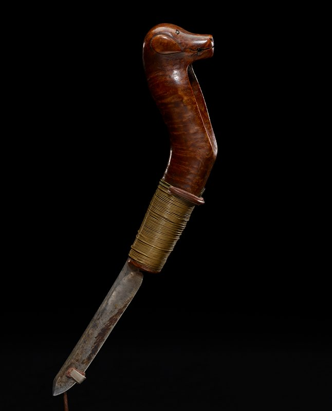 knife handle bent at midsection with indentation for thumb, with dog's head carved at end, with metal nailhead eyes; gold wire wrapped around portion of handle nearest blade; short blade; wooden sheath with leather belt loop; sheath carved from two pieces of wood joined together with gold wire; handle has slightly darker, richer patina than sheath--may be carved from two different types of wood