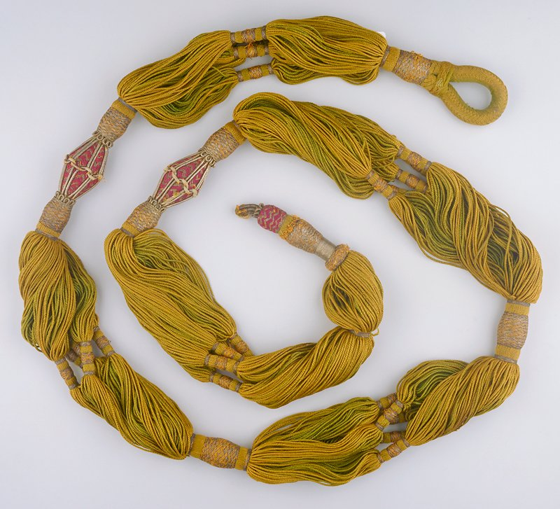 loose strands of twisted gold cords broken by small groups and the entire group bundled with silver metallic thread and 2 stiff diamond-shaped purple and silver twisted sections; loop on one end and 'button' on opposite end