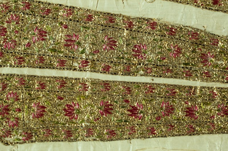 2 pairs of necktie shaped embroidery on white fabric; gold metallic ground with border and central section of floral vines in black, green, dark pink and light pink