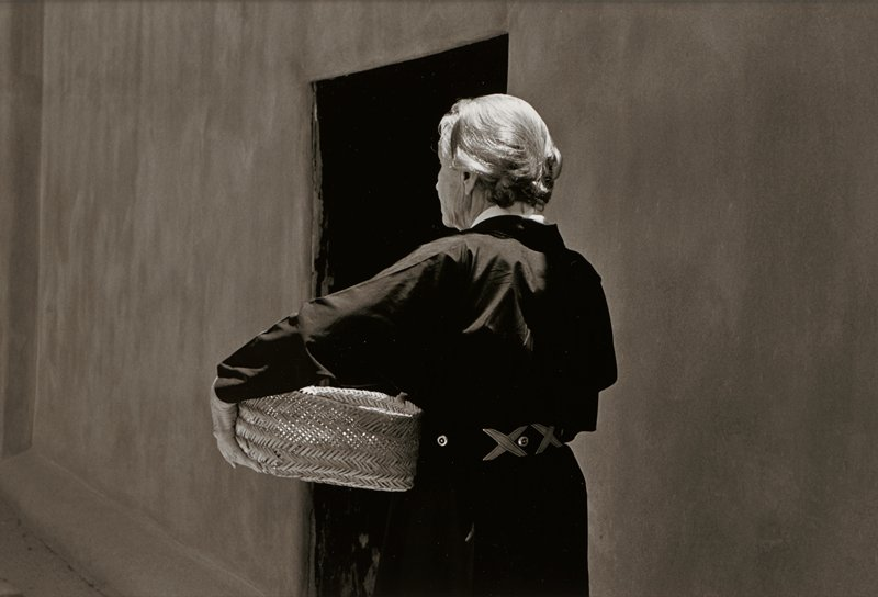 torso and head of elderly woman, seen from back, wearing a dark long-sleeved garment and belt with X's, carrying a basket; blank wall and doorway