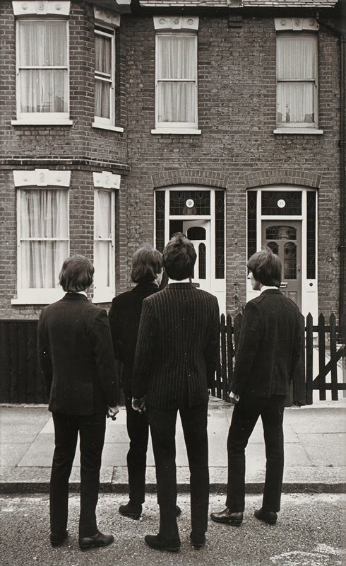 four men wearing dark suits (second man from right wears pinstriped jacket), seen from back, standing on street near sidewalk in front of brick building