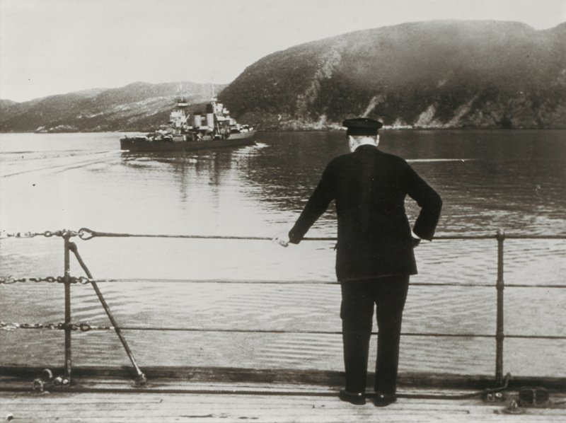 man wearing dark suit and cap, seen from back, with PR hand in pocket and PL hand resting on railing, looking over water at ship; tree-covered hills at horizon line