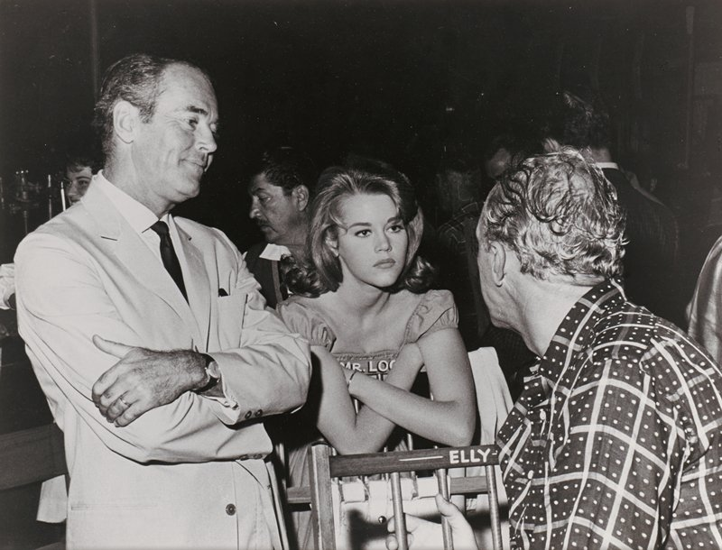 torso of man in profile from PL wearing a shirt patterned with checks and dots, with his head turned to PR; man has curly hair; head and torso of Henry Fonda, with arms crossed, wearing light suit and dark tie, at left; Jane Fonda, with a serious expression, leaning against the back of a chair, with her hands beneath her arms, at center; other figures in background