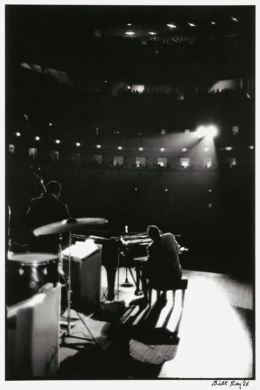 view from back of stage of man playing piano at center and man playing upright bass at left, with drum and cymbals in LLC; silhouetted figures in three balconies