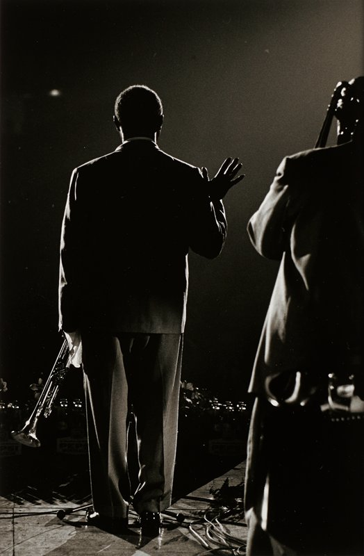 two men, both wearing suits, seen from back; man at left holds a trumpet in his PL hand and holds his PR hand up with fingers spread; man at right playing trombone