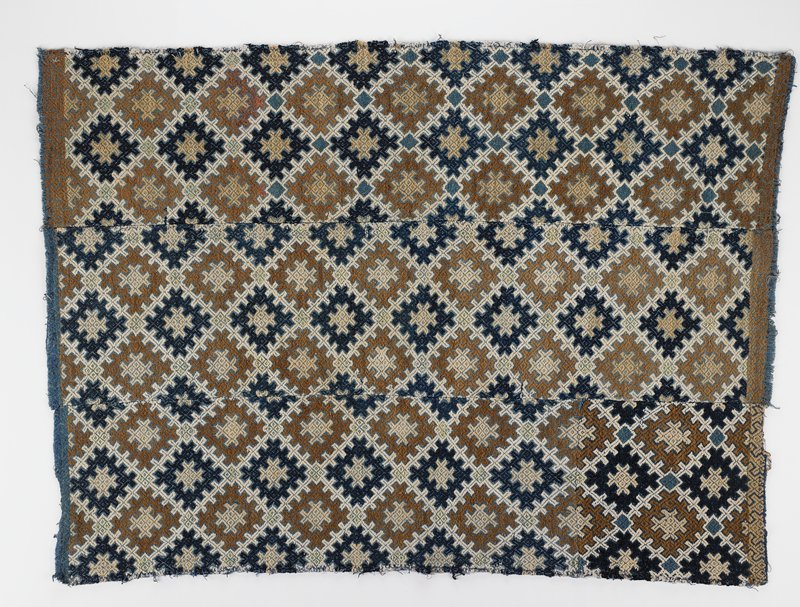 4 woven panels sewn together; geometric linear diamond design with brown, tan, white, light green and dark blue on medium blue ground