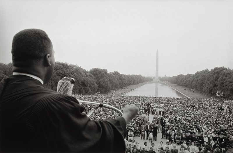 head, upper body and PR arm of black man at left, with PR hand in a fist, speaking into a plastic-covered microphone; crowds on the National Mall below him, with the Washington Monument in background