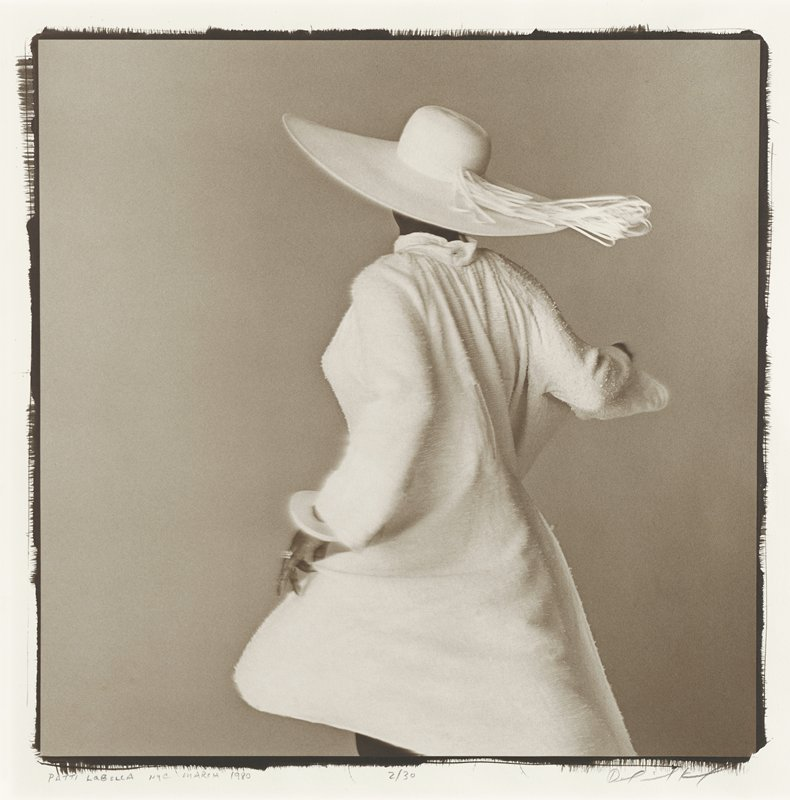 back of woman wearing a white coat, white hat with wide brim and ribbon and large white bracelet on her PL wrist, twirling; grey ground