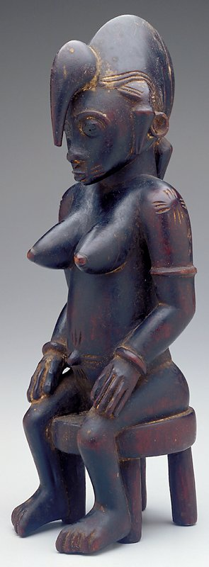 Female figure seated on a stool with hands resting on her thighs; helmet-like hairstyle