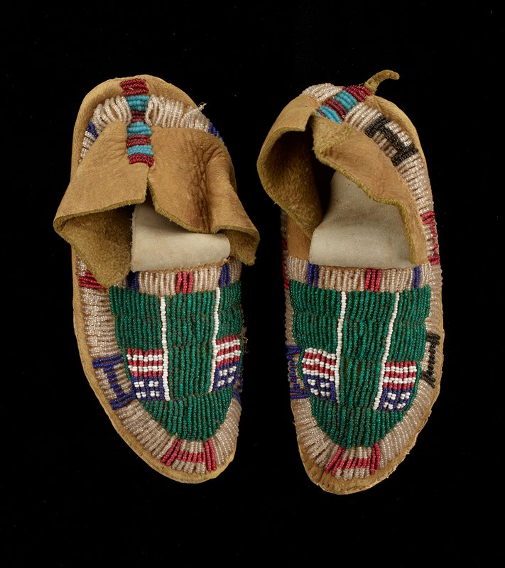 beading on top of each foot: green ground with two American flags; clear beaded band around side of each foot with alternating blue and red H's (two black H on left foot); vertical band of alternating beaded red and light blue strips up back of heel