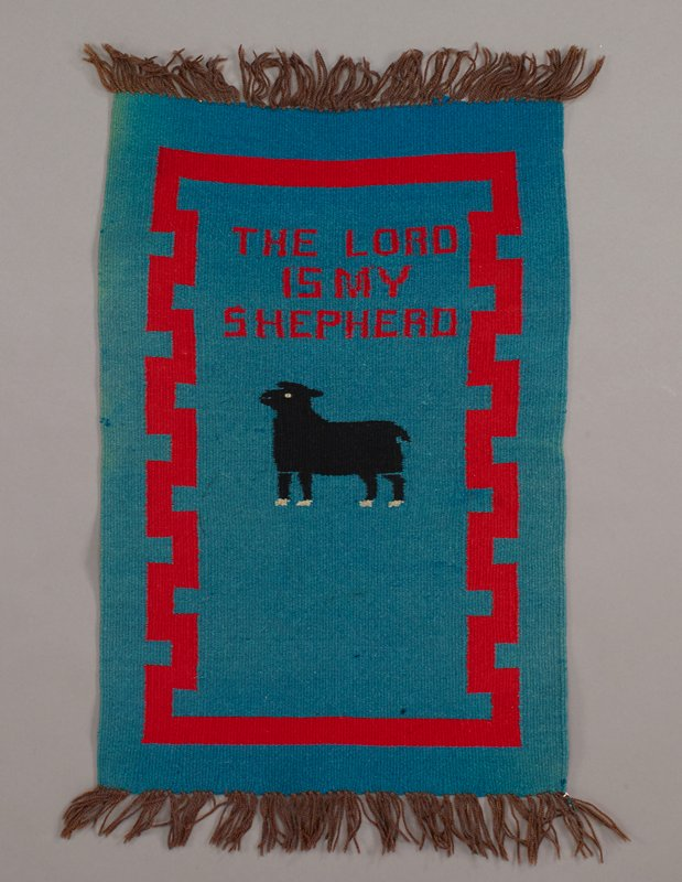 "blue ground with red border with stepped motif at long sides; red text at top: ""THE LORD IS MY SHEPHERD""; black sheep below text; brown fringe"