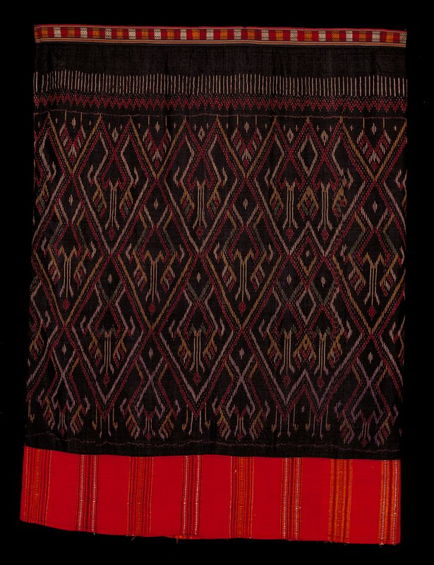 Waistband with black ground and yellow, red and white diamond design; skirt in black with ikat in red, yellow, white and green; hem in red with dots and stripes of yellow, green, black and white