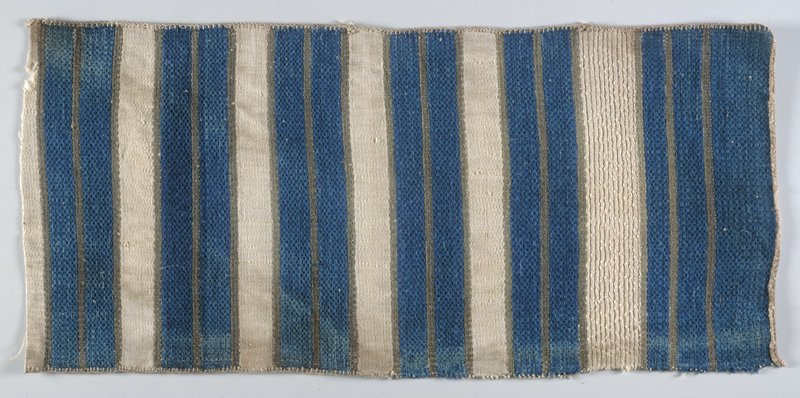 weft-float weave bands with indigo-dyed cotton on native ramie foundation; two indigo bands surrounded and separated by thin grey bands; white bands between; three sides finished, one side cut; bottom indigo bands vary slightly. Woven fabric