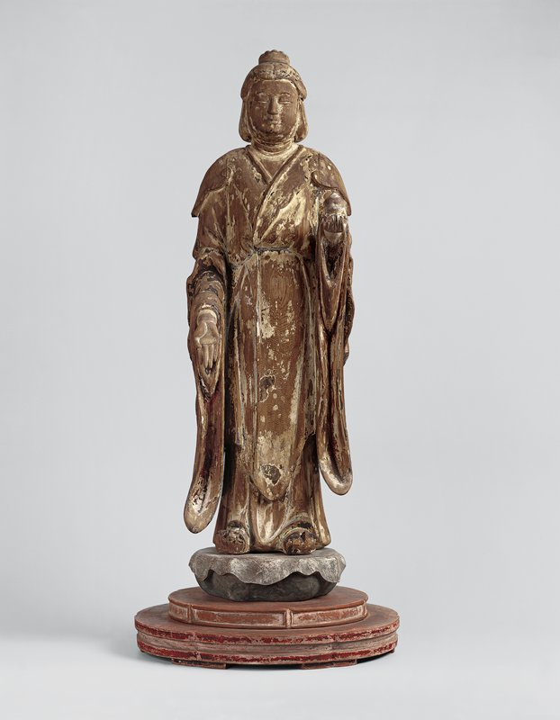 standing female figure holding a jewel in extended PL hand; holds PR hand open and down in blessing greeting; long robes with long, rippled sleeves; stands on red base
