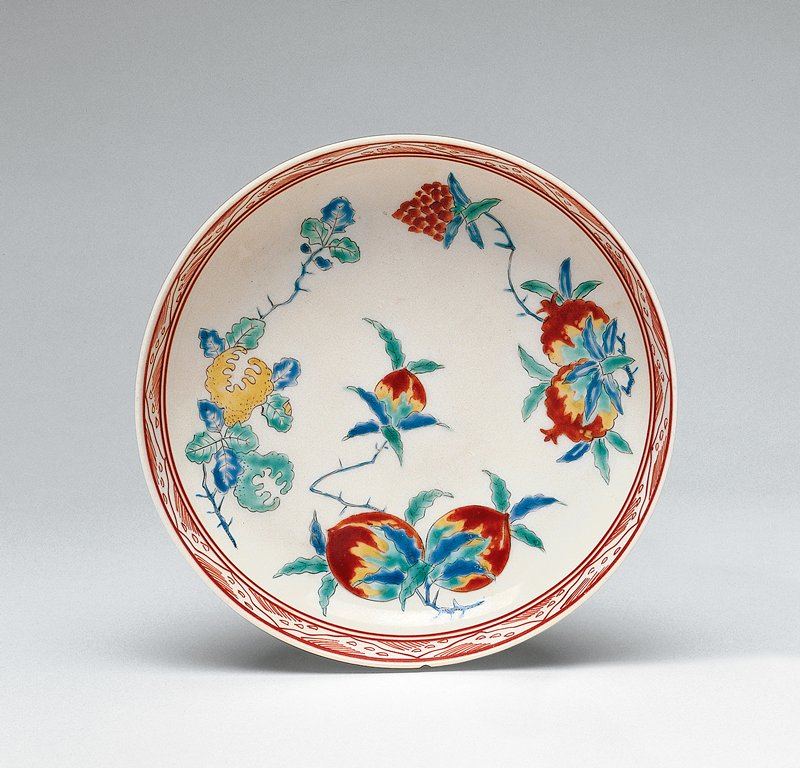 small dish with colorful fruits motif; red, yellow, green, and blue; delicate geometric design around inner lip