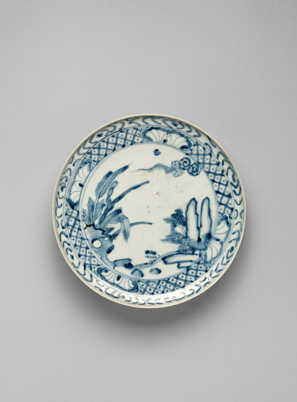 pale blue underglaze design of garden with small pavilion, trees, rock formation, banana trees, clouds; double border of cross-hatching with leaf design; outer border resembles wood grain; upturned edge