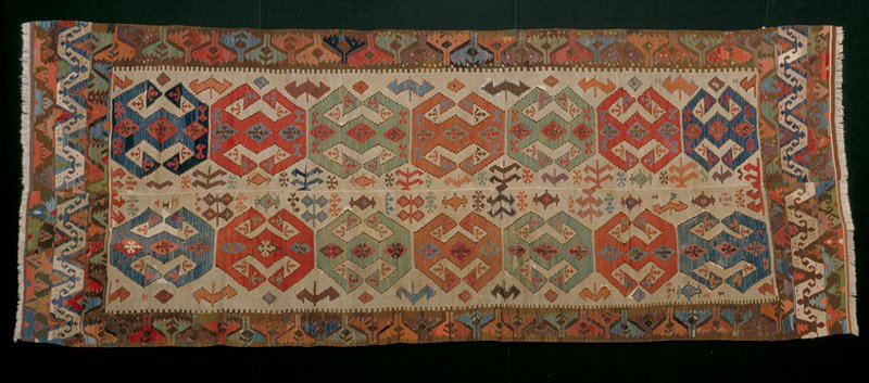 Geometric designs in brown, white, rust, blue, orange, green pink and red; background of central section in white with background in border in brown; 2 pieces sewn together lengthwise