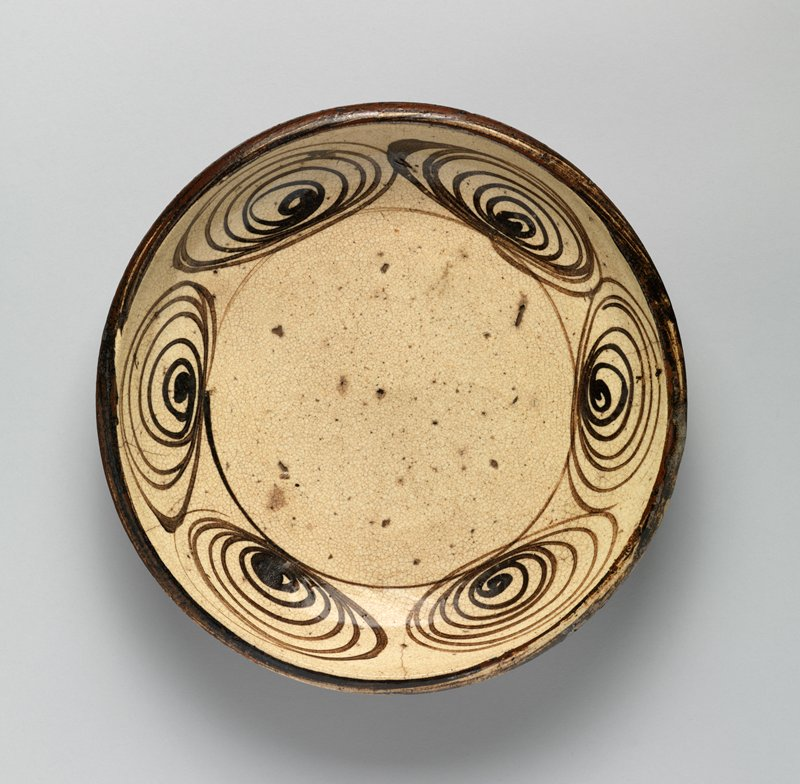 shallow dish with pattern of swirling ovals around inside in dark brown; dark brown lip