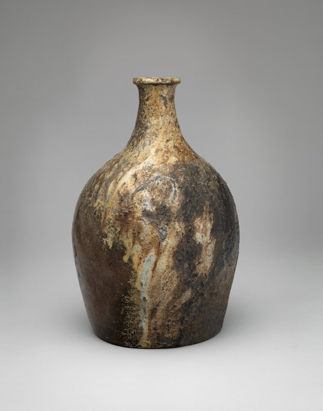 large bottle with relatively short neck from rounded shoulder; rust colored body with mottled, gritty, raised gray, ochre, cream overglaze