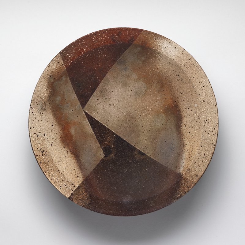 shallow dish with tan, square geometric pattern against rust and charcoal colored background