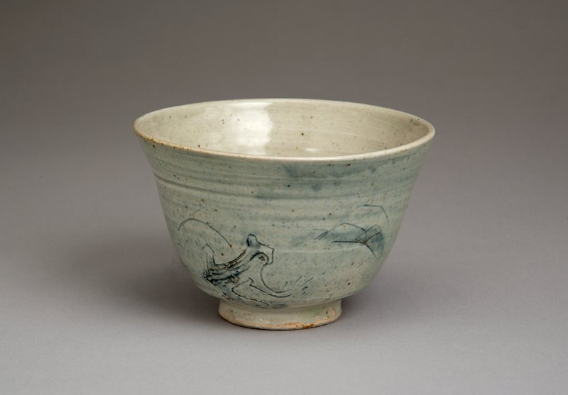 tea bowl with narrow base, flared mouth; pale blue glaze on outside; incised design of a frog looking up at a leaf; incised reeds