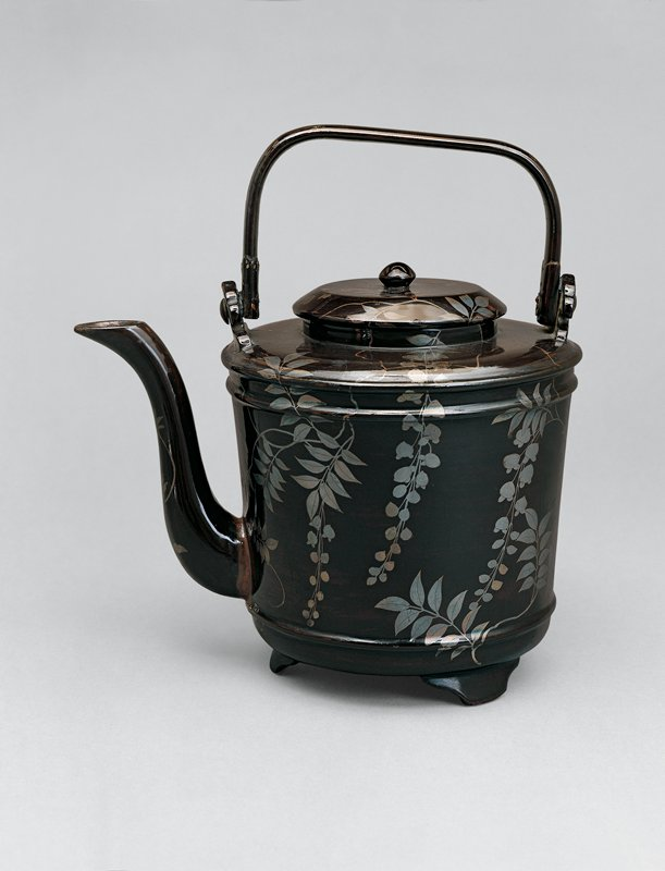 black lacquered covered pitcher with wisteria motif in silver; erect, squared handle, graceful spout; stands on three stout feet