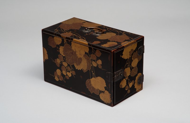 rectangular black lacquer box with grapevine design in gold and gold flecks; metal handle at top; hinges ad clasp on one of the shorter ends
