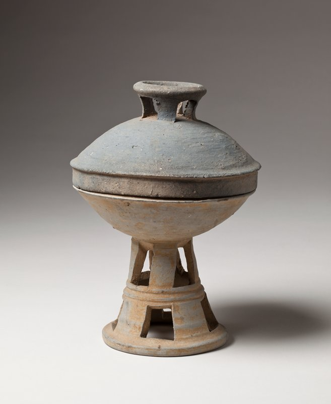 small bowl on conical stand; two layers of square cutouts on stand with a band of incised lines around center of stand; separate darker gray lid; raised knob with cutouts