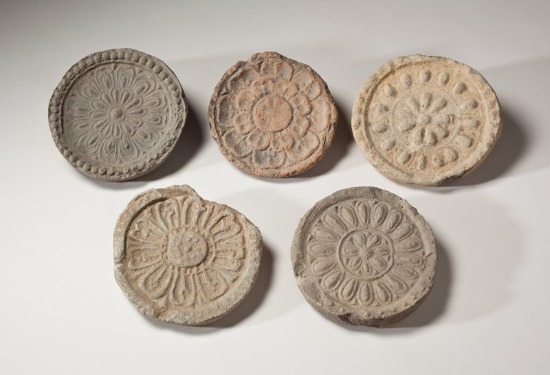 round roof tile end with floral design; small flower at center surrounded by low ribbed circle; larger petals with outlines around outer ring