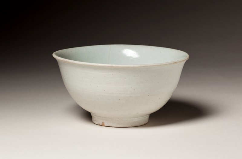 small bowl with outward flaring lip; shallow circular recess inside bottom of bowl; pale bluish-gray colored glaze; stands on short foot