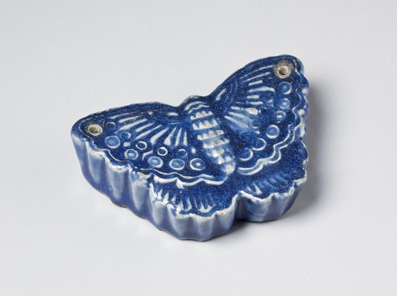 blue butterfly shaped porcelain water dropper; two small holes, one at the tip of each wing