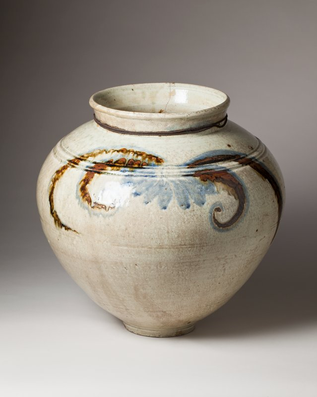 large jar with light brown and blue stylized flower and trailing leaf patterns on either side; iron cord around neck; two incised lines around shoulder; narrow foot, wide body, tapers at shoulder; short, rolled, slightly flared lip