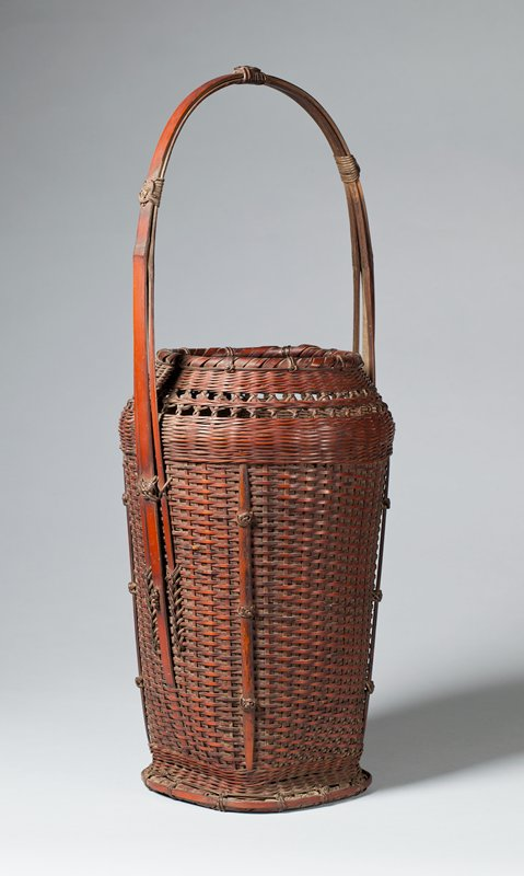 vertical rectangular basket with round neck and mouth; close horizontal weave with decorative crisscrossing weave around neck; decorative round knots around corners and on handle